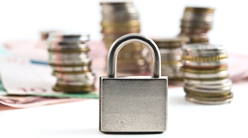 padlock with stacks of change in the background
